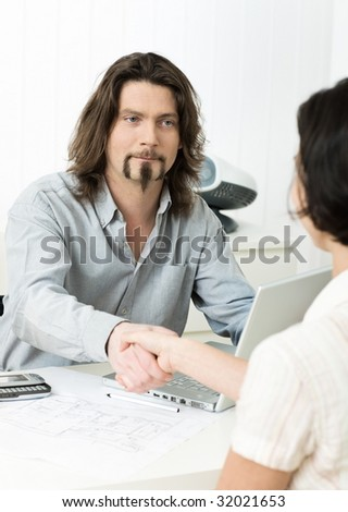 Businessman shaking hands with applicant during job interview in office. - stock photo