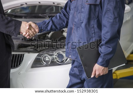 Businessman shaking hands with Mechanic in Auto Repair Shop - stock photo