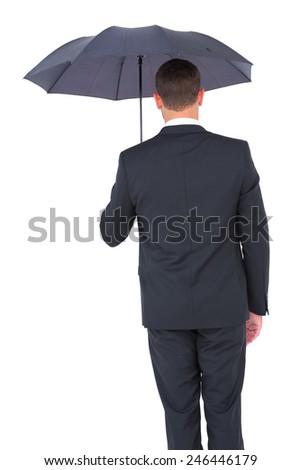 Businessman sheltering under black umbrella on white background - stock photo