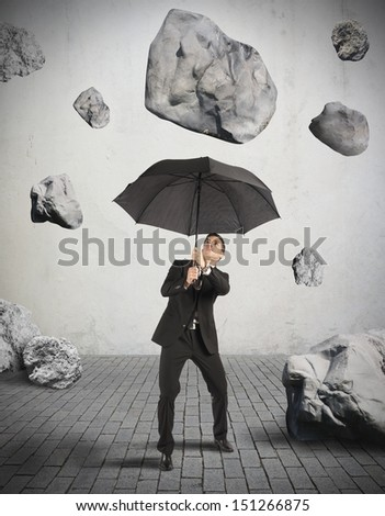 Businessman shelters from the storm of crisis