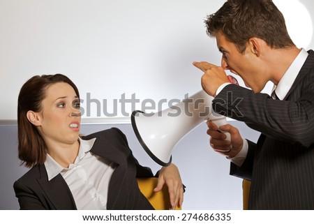 Businessman shouting at businesswoman through megaphone and gesturing gun sign - stock photo