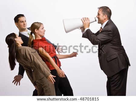 Businessman shouting at co-workers with megaphone - stock photo
