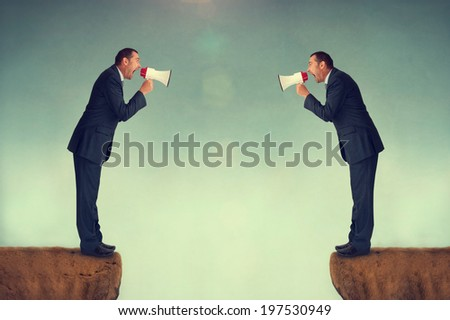 businessman shouting at each other through loudhailers or megaphones - stock photo