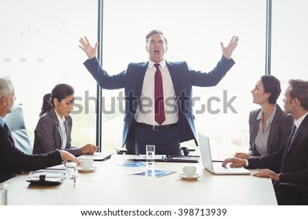 Businessman shouting at his colleagues in conference room during meeting - stock photo