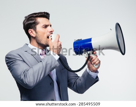 Businessman shouting in megaphone over gray background. Looking away - stock photo