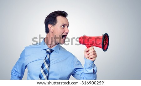 Businessman shouting into a red megaphone - stock photo
