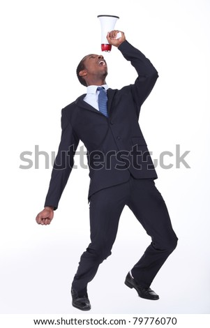 Businessman shouting into speaker phone - stock photo