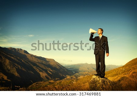 Businessman Shouting on the Top of the Mountain Concept - stock photo