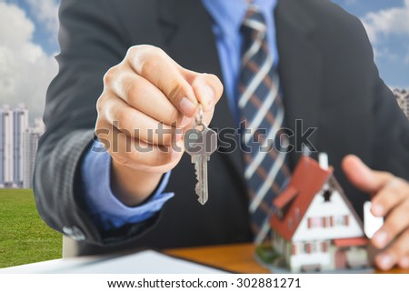 Businessman show Keys for your good property with real agency property. - stock photo