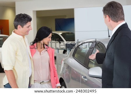 Businessman showing a car to a couple at new car showroom - stock photo