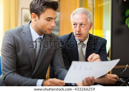 Businessman showing a document to his colleague - stock photo