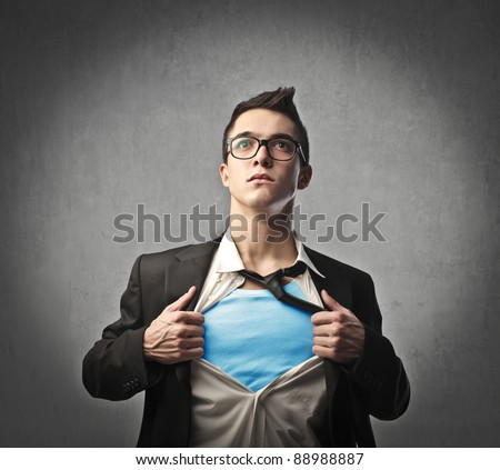 Businessman showing a superhero suit underneath his suit - stock photo
