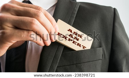 Businessman showing a wooden card reading - Ask an expert- as he withdraws it from the pocket of his suit jacket. - stock photo
