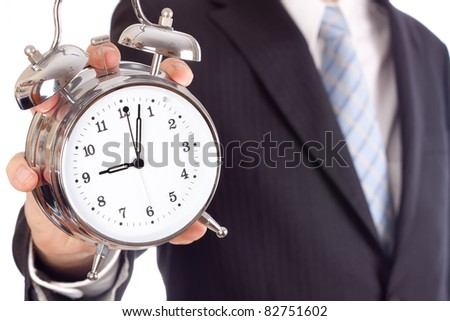 Businessman showing an alarm clock, aiming four past nine. - stock photo
