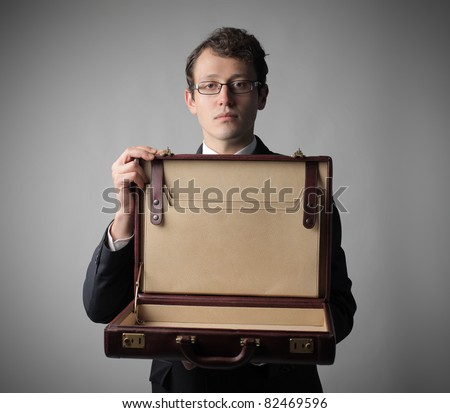 Businessman showing an empty briefcase - stock photo