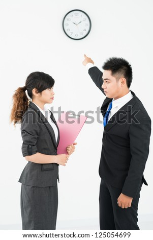 Businessman showing at clock for his colleague