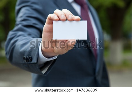 Businessman showing blank business card standing outdoors in a park - stock photo