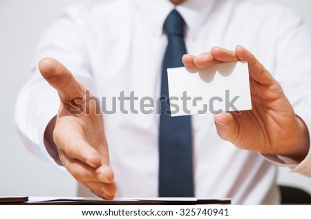 Businessman showing business card and offering handshake, closeup shot