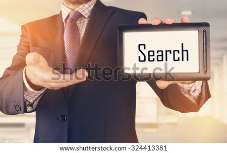 Businessman showing business concept on tablet standing in office - Search - stock photo