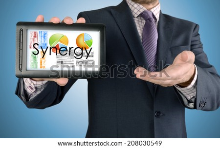Businessman showing business concept on tablet - Synergy - stock photo