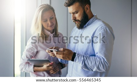Businessman showing business women information on smartphone screen. Woman holding digital tablet and looking on screen of phone. Businessmen discussing business plan. Teamwork, project preparation.