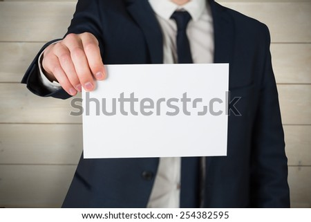 Businessman showing card to camera against bleached wooden planks background - stock photo