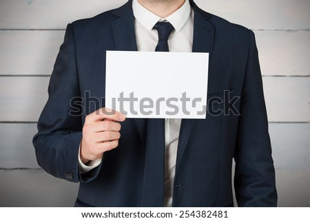 Businessman showing card to camera against painted blue wooden planks