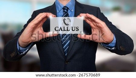 Businessman showing card with Call Us text. Phone icon. Communication concept. Isolated on office. Stock Image - stock photo