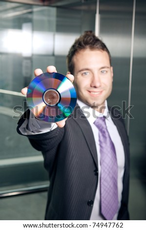 Businessman showing CD or DVD - stock photo