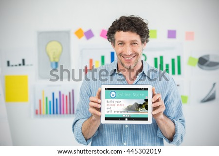 Businessman showing digital tablet with blank screen in creative office against screen of an online store - stock photo