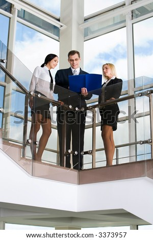 Businessman showing documents to his colleagues on stairs in the building with glassy walls - stock photo