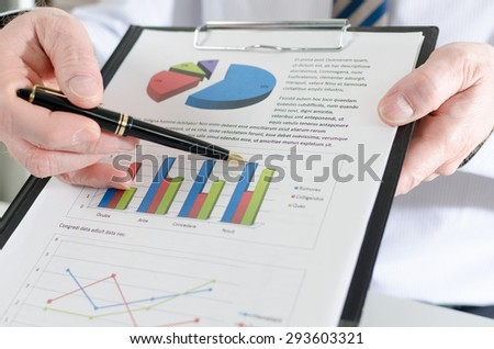 Businessman showing financial results on a clipboard - stock photo