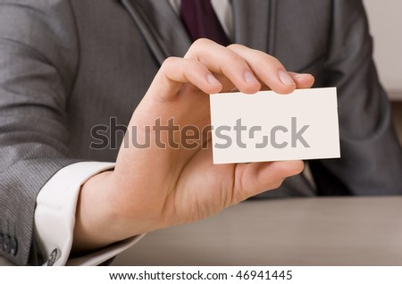 Businessman showing his business card. Shallow depth of field - focus on fingers and card. You can just add your text there.