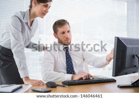 Businessman showing his colleague something on computer at desk in office - stock photo