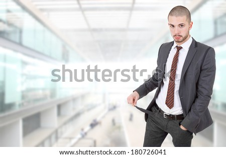 businessman showing his empty pocket at the office - stock photo
