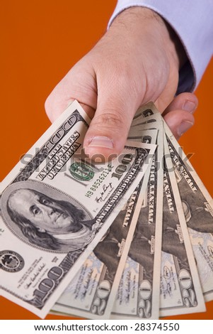 businessman showing his money with a orange background (selective focus)