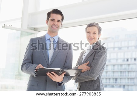 Businessman showing his notes to his colleague in the office - stock photo