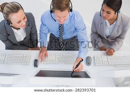 Businessman showing his screen to the team in call center - stock photo