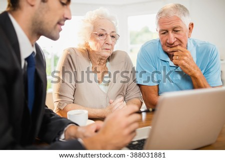 Businessman showing laptop to senior couple at home - stock photo