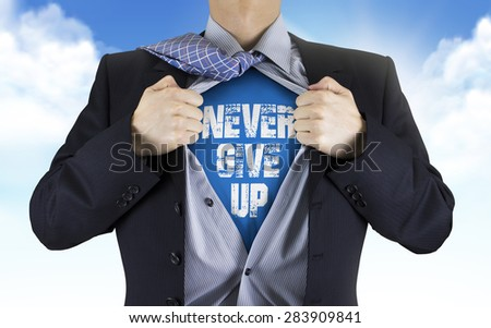 businessman showing Never give up words underneath his shirt over blue sky - stock photo