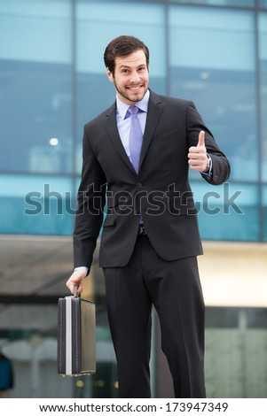 businessman showing ok sign in front of an office building - stock photo