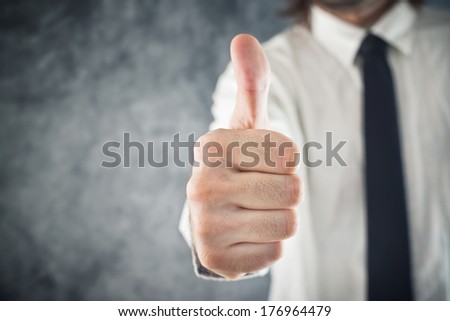 Businessman showing OK sign with his thumb up, selective focus - stock photo