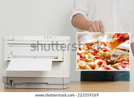 Businessman showing printed paper near color printer on table in office
