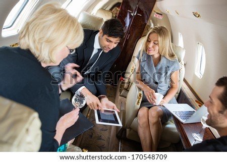 Businessman showing project on digital tablet with colleagues in private jet - stock photo