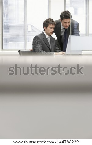 Businessman showing project to male colleague on laptop in the office - stock photo