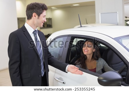 Businessman showing something to a woman at new car showroom - stock photo