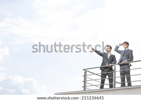 Businessman showing something to coworker against cloudy sky - stock photo