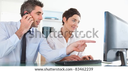 Businessman showing something to his coworker on a computer in an office - stock photo