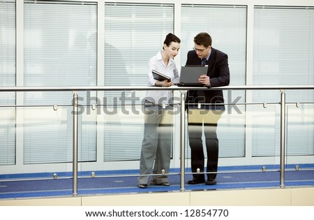 Businessman showing something to young businesswoman in his laptop on modern office corridor. - stock photo