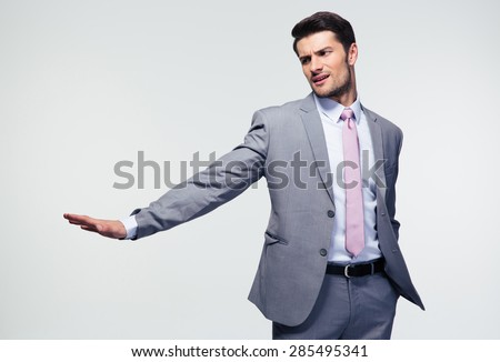 Businessman showing stop gesture with palm over gray background - stock photo